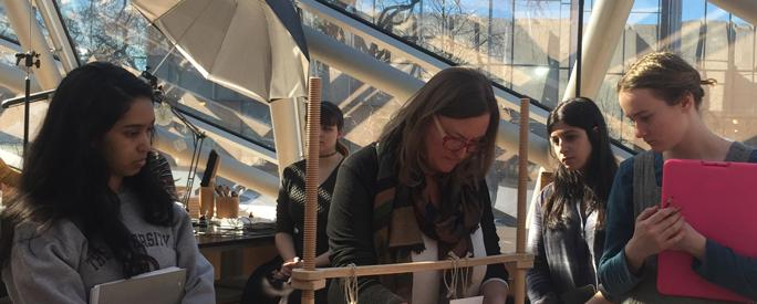"Ann Lindsey, Head of Conservation at the University of Chicago Library, demonstrating manuscript binding to UChicago students."" or ""UChicago students observing demonstration of manuscript binding by Ann Lindsey, Head of Conservation at the University of Chicago Library."