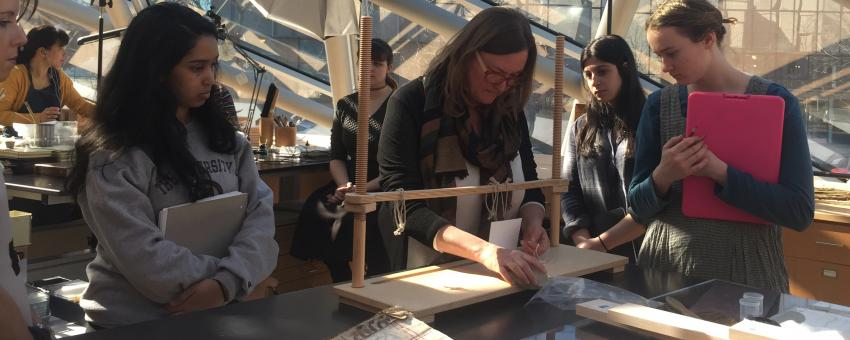 "Ann Lindsey, Head of Conservation at the University of Chicago Library, demonstrating manuscript binding to UChicago students."" or ""UChicago students observing demonstration of manuscript binding by Ann Lindsey, Head of Conservation at the University of Chicago Library"