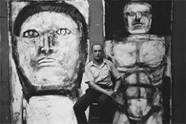 "Leon Golub photographed in the 1950s in front of two paintings from his ""Philosophers"" series COURTESY THE NANCY SPERO AND LEON GOLUB FOUNDATION FOR THE ARTS"